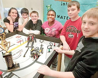"""SMILES ALL AROUND: Members of the Lego Lizards of Girard Junior High School gather around the board on which """"Lizzy,"""" the team's robot travels. Students, from left, are Gabby Cloggins, Nick Sherock, Cameron Blenton, Jalene McClendon, Brian Spence and David Kuzman. They won the Quality Design Award in the FIRST Lego League regional competition in Canton. The trophy is at left."""