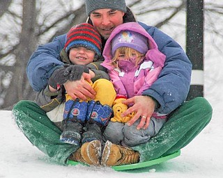 While Mahoning Valley drivers were cursing the white stuff coating area roads Thursday, some kids managed to find the silver lining in the snow clouds that blanketed the Northeast. Above, Adam Gardner, with his children Caleb, 4, and Sophie, 2, all of Warren, slide down a snowy hill at Packard Park in Warren.