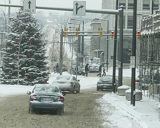 Motorists and pedestrians brave the elements in downtown Youngstown Friday morning.