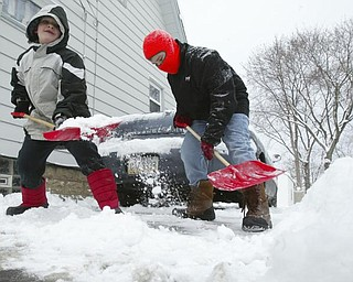 Brothers Declan, 7, left, and Isaiah Sekol shovel the driveway of their Struthers home on Maplewood Friday morning.
