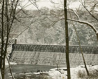 The Vindicator/Robert K. Yosay -----Breath of winter as water flows over the damn near the Pioneer Cabin in Mill Creek MetroParks. with snow covering the evergreens.