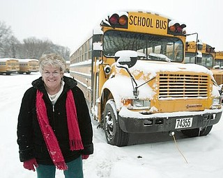 Judi Ebert, of Boardman, stands alongside a parking lot full of snow covered buses, after picking up her paycheck at the Youngstown Board of Education's Bus Depot on Friday afternoon. Ebert, a nine year veteran driver, and her fellow drivers had the day off on Friday with all or nearly all of Mahoning County's schools closed due to snow fall and freezing conditions. Despite having the day off, after picking up her check, Ebert was off to shuttle her friends children to the YMCA despite having the day off.