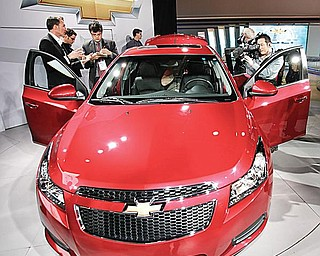 The press gets a close look at the 2011 Chevrolet Cruze after its unveiling at the Los Angeles International Auto Show in Los Angeles. It debuted there last month. This week, the Lordstown-built car is featured at the North American International Auto Show in Detroit.