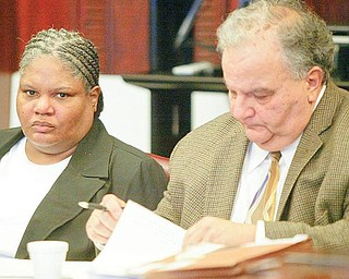 ON TRIAL: Monique Williams of Youngstown sits at the defendant's table in Mahoning County Common Pleas Court. She is on trial in the death of her husband, Julius. Seated next to her Thursday was her lawyer, Atty. Thomas E. Zena.