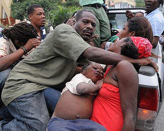 Injured people are carried away in a truck after an earthquake in Delmas, Haiti, Wednesday, Jan. 13, 2010.  A 7.0-magnitude earthquake, the largest ever recorded in the area, rocked Haiti on Tuesday.