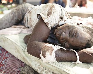 An earthquake survivor lies on a matt on a street of Port-au-Prince, Thursday, Jan. 14, 2010.