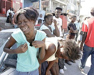 Girls cry as a little girl is removed from the rubble, Wednesday, Jan. 13, 2010, in Port-AU-Prince, Haiti.  Tuesday's quake left a landscape of collapsed buildings _ hospitals, schools, churches, ramshackle homes, even the gleaming national palace _ the rubble sending up a white cloud that shrouded the entire capital.