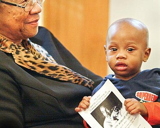 STARTING YOUNG: Daniel Harris, 1, of Youngstown takes in a community worship service to honor the Rev. Martin Luther King Jr. He was sitting in the lap of Louise Sullivan as his mother sang in the choir Sunday. The service was at Elizabeth Missionary Baptist Church in Youngstown.