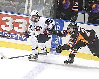 I'LL TAKE THAT: Ben Paulides (27) of the Youngstown Phantoms tries to keep the puck from Team USA's Austin Wuthrich during Monday's game at the Covelli Centre. The Phantoms won 7-3.