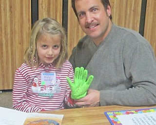 Reading is fun when you can make personalized gloves to wear. Molly Malmer (left) sits with her father, Mike Malmer, and shows off the reading glove that she made.