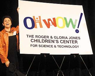 """NEW LOGO: Suzanne Barbati, executive director of """"OH WOW!"""" The Roger & Gloria Jones Children's Center for Science & Technology, unveils the new logo for the former Children's Museum of the Valley. The center has launched a $1.5 million campaign to remodel and furbish its new home, the former McCrory Building in downtown Youngstown."""