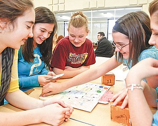 """The Vindicator/Lisa-Ann Ishihara ---Boardman Glenwood Middle School students L-R Natalie Wilson (12) Krista Johnson (12) Andrea Gardner (12) Emily Buledorn (11) and Kara Seeco (11)  play the game they made """"Lost Crown"""" Wednesday afterschool ."""