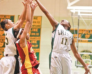 The Vindicator/Lisa-Ann Ishihara--- Ursuline Aurielle Irizarry (5) and Kaneesha Tensley (11) and Mooney Chyna Davis (3) go after the rebound during the second period Thursday night.