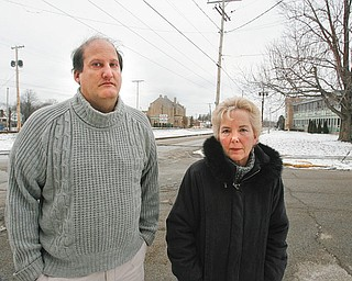NEIGHBORHOOD WOES: Longtime South Side residents Terry Esarco, 50, left, and Maggy Lorenzi, 58, right, stand just up the street from St. Dominic Church, center, where 80-year-old Angeline Fimognari was shot and killed Saturday morning. Lorenzi said she's lived on the South Side of Youngstown for 50 years and has seen the neighborhood deteriorate.