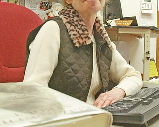 """MULTI-TASKER: Kim Mozley, who has volunteered at Hubbard Area Public Library for 13 years, contributes a variety of services including processing books for the inter-library loan system, readying books and tapes for circulation by covering with plastic cases and date-due stickers, doing database maintenance and looking for """"lost"""" materials on shelves."""