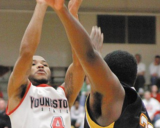 OVER THE TOP: YSU's Vance Cooksey (4) gets a shot off over Milwaukee's Jerard Ajami (30) during the first half Friday at Beeghly Center.