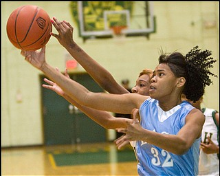 The Vindicator/Geoffrey Hauschild.East's Reshayla Taylor (32) struggles for the ball with Ursuline's Dominique Jenkins (15) during the second quarter of a game at Ursuline High School on Thursday evening.