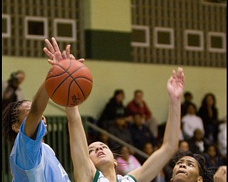 The Vindicator/Geoffrey Hauschild.Ursuline's Ja'Niece Whitehead (14) struggles for a rebound with East's Briana Dawson (10) Reshayla Taylor (32) during the second quarter of a game at Ursuline High School on Thursday evening.
