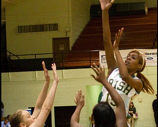 The Vindicator/Geoffrey Hauschild.Ursuline's Dominique Jenkins (15) takes a shot while defended by East's Bethany Hines (15) and Lesa Monet Oliver (22) during the third quarter of a game at Ursuline High School on Thursday evening.