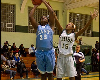 The Vindicator/Geoffrey Hauschild.East's Lesa Monet Oliver (22) scores two while defended by Ursuline's Dominique Jenkins (15) during the third quarter of a game at Ursuline High School on Thursday evening.