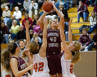 The Vindicator/Geoffrey Hauschild.Boardman's Kayleigh Lipke (40)shoot over top of Hoover's Alyssa Chovan (42) and Lindsey Fiala (24) during the third quarter of a game at Hoover High School on Saturday afternoon.