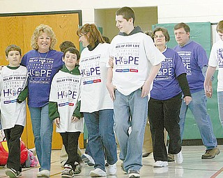 SURVIVOR WALK: Members of the Fisher family joined their adopted grandma, Patty Boyle, for her survivor walk at the Relay for Life at St. Patrick School in Hubbard. From left, John, 12;  Patty Boyle; Joe, 10; Michelle; and Billy, 13, walk in the gymnasium at St. Patrick School.