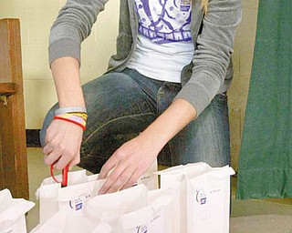 LIGHTING LUMINARIA: Allison Naples, a senior at Ursuline High School, lights the first of many luminarias during the Relay for Life event at St. Patrick School in Hubbard.