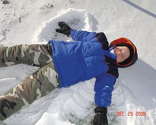 Preston English of Boardman, 41Ú2, makes snow angels in the snow..