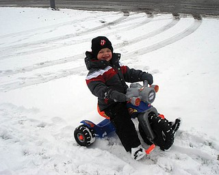 John Darnley, 3, of Mineral Ridge, is playing in the snow on his motorcycle..
