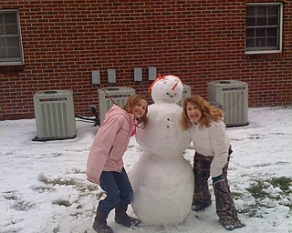 Friends Annamarie Duda, of Berlin Center, and Raquel Markulin, of Canfield, build a snowman together.