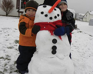 Brothers Braden Butler, 5, and Evan Butler, 3, of New Middletown built their first snowman. .