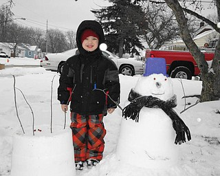 Vincent Dominic from Youngstown shows off his snow birthday cake and his first snowman..