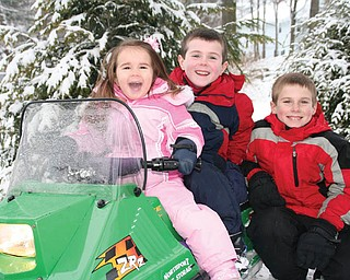 Lauren, Christopher and Bobby Smallwood, all of Canfield., take time out for a photo while riding their snowmobile..