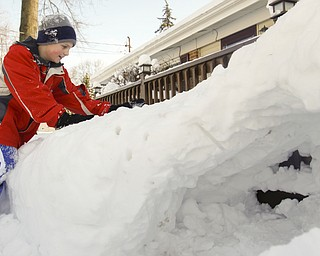 The Vindicator/Lisa-Ann Ishihara--- Tyler Evans (10) of Austintown packs more snow on top of the fort his father help him make.