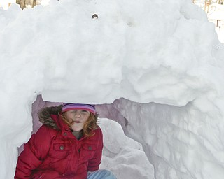 The Vindicator/Lisa-Ann Ishihara--- Emily Evans (5) of Austintown sits in the fort her father helped make, while her brother Tyler (10) packs more snow above.