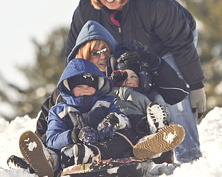 The Vindicator/Lisa-Ann Ishihara--- Tracy Ward of Girard gives her sister, Melissa Ward of Liberty, and nephews Evan (5) and Zach (3) a push down the hill in the snow at Mill Creek Park's  Wick Recreation Area .