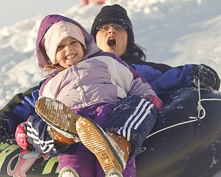 The Vindicator/Lisa-Ann Ishihara--- Cindy Bakos of Austintown and her daughter Kylie (5)  slide down the hill in the snow at Mill Creek Park's  Wick Recreation Area .