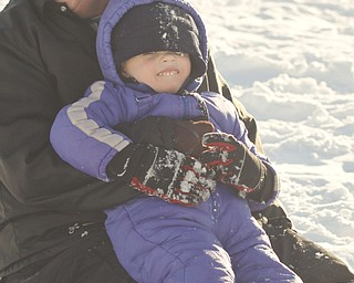 The Vindicator/Lisa-Ann Ishihara--- Danielle Mackall of Austintown holds Colin Bakos (3) after  sliding backwards down the hill in the snow at Mill Creek Park's  Wick Recreation Area .
