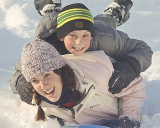 The Vindicator/Lisa-Ann Ishihara--- Rory Sachire (18) and Tanner Mackall (10) of Austintown slide down the hill in the snow at Mill Creek Park's  Wick Recreation Area .
