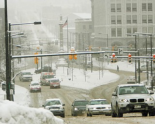 WINTER WOES: Snow did not let up all day Wednesday, creating challenges for road crews and motorists, such as those motoring on Wick Avenue near Youngstown State University.