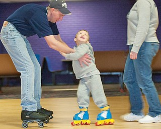 The Vindicator/Geoffrey Hauschild.Jodi Sweeney and Carl Bond, of Boardman, help their son, Jordan Bond, 3, use the roller skates he received as a Christmas gift at a rink for the first time at Skate Zone in Austintown on Thursday afternoon..1.21.2010.Skate Zone InFocus
