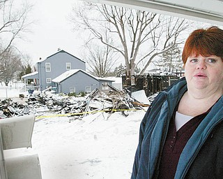MEMORIES OF AN EXPLOSION: Jodi Hunt stands on the front porch of her home on Center Road as she recounts the events leading up to the home next door to hers exploding Saturday. The charred remains of the neighboring house can be seen in the background.