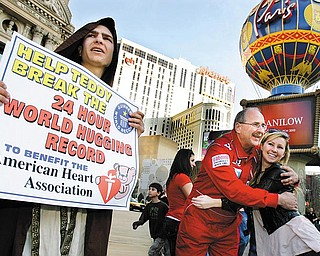 Jeff Ondash, nicknamed Teddy McHuggin, hugs a tourist as Joshua Dietrich, left, holds a sign on The Strip in Las Vegas on Saturday, February 13, 2009. Ondash set the Guinness World Record for hugs in a 24 hour period and succeeded in giving 7,777 hugs.