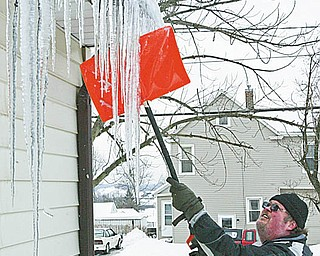 DOn'T DO THIS: David Kovach knocks down icicles on his Plymouth Street home in Girard. Roofing and gutter company officials say don't do it to avoid possible injury and damage to your home.