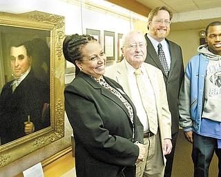 William D. Lewis/The Vindicator l-r Dr. Wendi Webb, Y-town Schools Supt. Charles Rudibaugh, Rayen Foundation President, William Lawson of Arms Museum and East HS senior Brandon Mosley, who was a freshman at Rayen before it was closed look over items at the Rayen exhibit at the Arms Museum. Portrait of Judge William Rayen is at left.
