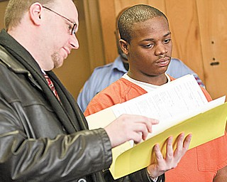 PAPERWORK: Jamar Houser, 19, right, looks over copies of the charges against him with his lawyer, Atty. Michael Villani, in Youngstown Municipal Court. Houser, a suspect in a murder case, was sentenced Thursday to 90 days in Mahoning County jail on unrelated charges of disorderly conduct and criminal damaging.
