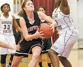 Canfield's Sabrina Mangapora (44) drives to the hoop past Boardman's  Darryce Moore (44) only to be fouled during the third quarter of a game at Boardman High School on Thursday evening.