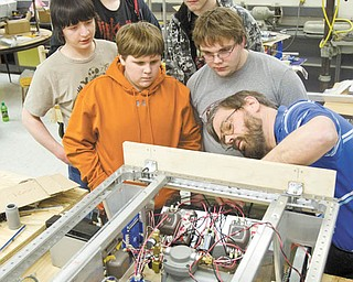 A WIRING LESSON: Teacher adviser Gordon Powell, far right, shows the Liberty High School robotics team how to run wire through drilled holes. Team members watching, from center going counterclockwise, are: Carter Brady, 15; Nate Purnell, 17; Steve Struble, 16; Rick Palmer, 15; and Adam Clare, 14.