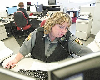 COLUMBIANA UPGRADES: Jennifer Swords, a Columbiana County 911 dispatcher, handles a call. The county is upgrading its 911 emergency telephone service so that it can handle calls made from cellular phones.