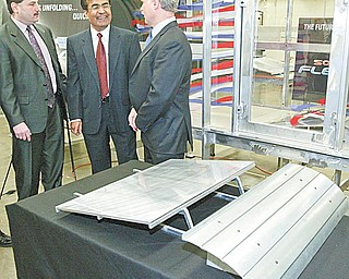 WIND TUNNEL TESTING: From left, Abraham; Ganesh Kudav, a YSU engineering professor; and Robert Voytilla, chief financial officer for Northern States Metals, discuss a wind tunnel at YSU used for testing the effectiveness of wind deflectors in the installation of rooftop solar-energy panels manufactured by Northern States. The company built the tunnel for YSU to use in the development of the deflector, a model of which is in the foreground.